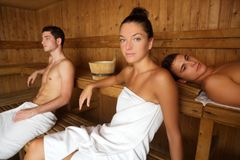 Sauna spa therapy young group in wooden room. Sauna spa therapy young people group in warm wooden room white towel stock photos