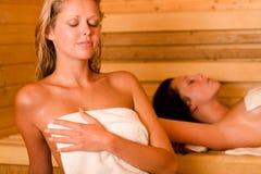 Sauna twee vrouwen die het zweten behandelde handdoek ontspannen Stock Foto's