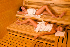 Sauna two women relaxing lying wrapped towel Royalty Free Stock Photo