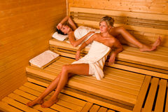 Sauna two women relaxing lying wrapped towel Royalty Free Stock Image