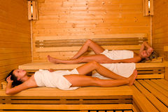 Sauna two women relaxing lying wrapped towel Royalty Free Stock Images