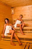 Sauna two women relaxing sitting wrapped towel Royalty Free Stock Image