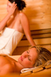 Sauna two women relaxing sweating covered towel Royalty Free Stock Photo
