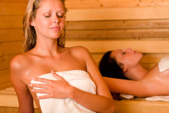 Sauna two women relaxing sweating covered towel Stock Photos