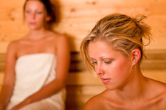 Sauna two women relaxing sweating covered towel Stock Photo