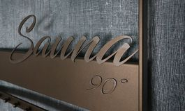 Sauna volumetric lettering decoration inscription at the spa hot. El. Entrance sign Sauna title type at the wellness center, closeup Royalty Free Stock Images