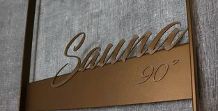 Sauna volumetric lettering decoration inscription at the spa hot. El. Entrance sign Sauna title type at the wellness center, closeup Royalty Free Stock Photos