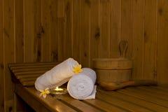 Saunabank mit weißen Tüchern und Eimer Lizenzfreie Stockbilder