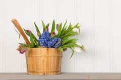 Saunaeimer mit Blumenstraußblumen lizenzfreie stockbilder