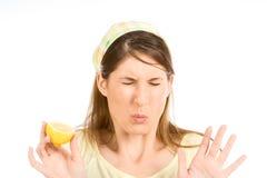 Saure Grimasse der jungen Frau mit Hälfte der Zitrone Stockfotografie