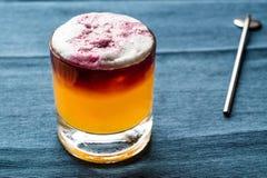 Saures Cocktail New York mit Schaum und blauem Hintergrund stockbild