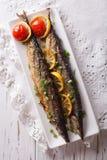 Saury grillade med grönsaker på en plattanärbild Lodlinjeöverkant Royaltyfri Bild