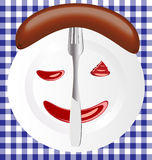 Sausage. Against the background of a large white dish appetizing sausage with the sauce and fork Stock Photo