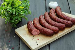 Sausage. Appetizing sausages arranged on the table and board Stock Photos