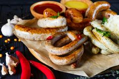 Sausage assortment on black background decorated with garlic, pe stock image
