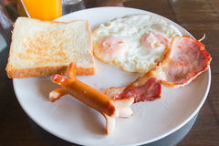 Sausage, bacon, double eggs, and white bread toast for breakfast Stock Images