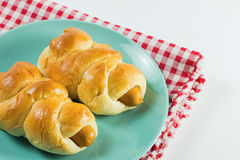 Sausage baked in dough on the green dish put on fabric white, red. White background Royalty Free Stock Photos