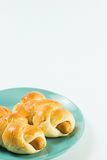 Sausage baked in dough on the green dish. Sausage baked in dough on the green dish white background Stock Images