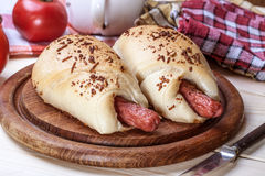 Sausage baked in dough. Sausage baked in dough on a wooden chopping board royalty free stock images