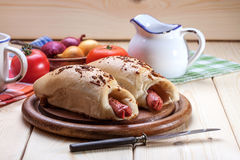 Sausage baked in dough. Royalty Free Stock Image