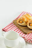 Sausage baked in dough on wooden plate with cup coffee. Sausage baked in dough on wooden plate put on fabric white, red with cup coffee. white background Stock Photo