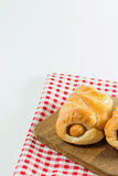 Sausage baked in dough on wooden plate. Put on fabric white, red. white background Royalty Free Stock Images