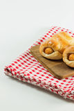 Sausage baked in dough on wooden plate. Sausage baked in dough on wooden plate put on fabric white, red. white background Stock Photography
