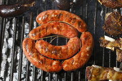 Sausage barbecuing on the grill Stock Photography