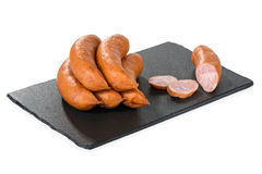 Sausage on a black stone tray isolated on white Royalty Free Stock Photography