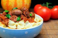SAUSAGE AND BOW TIE PASTA DINNER. Maple breakfast link sausages in a tomato sauce on Farfalle pasta with basil Royalty Free Stock Photography