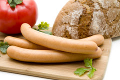 Sausage with bread. Sausage with tomato and bread on edge board royalty free stock photos