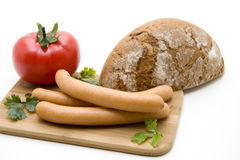 Sausage with bread. Sausage with tomato and bread on edge board Royalty Free Stock Photo