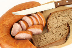 Sausage with bread. Breakfast close-up. Slices of sausage and bread on the wooden plate with kitchen knife Stock Photos