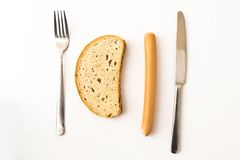 Sausage, bread and cutlery Stock Image