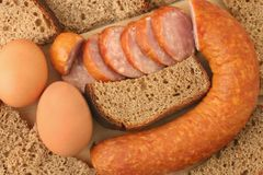 Sausage, bread and eggs. Breakfast close-up. Slices of sausage, bread and brown eggs Stock Photography
