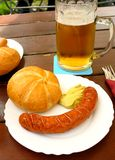 Sausage with bread and mustard in beer garden Stock Images