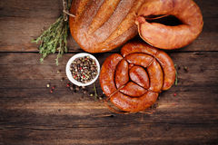 Sausage. Bread and spices on a wooden table royalty free stock image