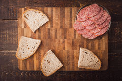 Sausage and bread on the wooden board top view Royalty Free Stock Images