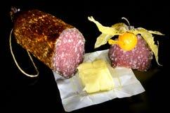 Sausage, butter and physalis Stock Photos