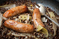 Sausage casserole. Sausages cooked with lentils, fennel and fresh leeks in a one pot casserole. Served on a rustic wooden table Royalty Free Stock Image