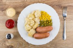 Sausage with cauliflower, sweet corn, green peas, sauces on tabl Royalty Free Stock Photo