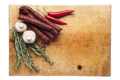 Sausage and chilli on a cutting board. Wooden cutting board with sausages and chilli, top view Royalty Free Stock Photography