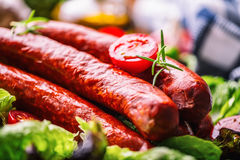 Sausage. Chorizo sausage. Raw smoked sausage with vegetable decoration.Lettuce salad herb rosemary tomato garlic olive oil Stock Images