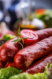 Sausage. Chorizo sausage. Raw smoked sausage with vegetable decoration.Lettuce salad herb rosemary tomato garlic olive oil Royalty Free Stock Photography