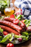 Sausage. Chorizo sausage. Raw smoked sausage with vegetable decoration.Lettuce salad herb rosemary tomato garlic olive oil Royalty Free Stock Images
