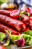 Sausage. Chorizo sausage. Raw smoked sausage with vegetable decoration.Lettuce salad herb rosemary tomato garlic olive oil Stock Image