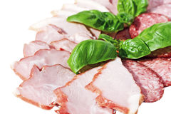 Sausage and cured meat. Cutting sausage and cured meat with a basil Stock Photos