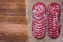 Sausage cut into circles on the paper. Natural wooden background. Royalty Free Stock Photo