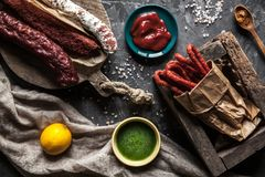 Sausage on a dark background with elements of cooking. Cucumber, onion, ketchup royalty free stock photo