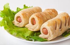 Sausage in the dough. On a plate with greens Stock Image